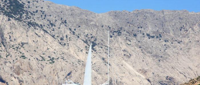 barca a vela con dietro il costone di tavolara